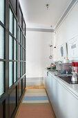 Narrow kitchen separated by black lattice and glass partition