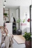 White-tiled, Bohemian-style bathroom with houseplants and wicker chair
