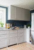 White cupboards in kitchen with petrol-blue walls
