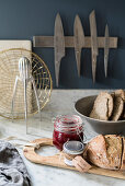Jam and bread on wooden board on marble worksurface below magnetic knife rack on blue-grey wall