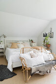 Double bed and rattan bench with cushions in white attic bedroom