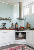 Cooker with modern, stainless steel extractor hood in corner of kitchen with pale blue wall tiles