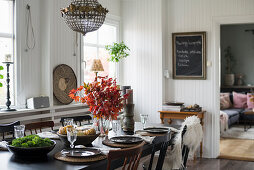 Dining table set for autumn dinner in interior with white wood-panelled walls