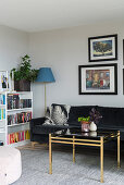 Black velvet couch and brass coffee table next to bookshelves in living room