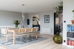 Pale wooden table and cane cantilever chairs in dining area