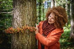Frau im Wald bindet Girlande aus Hagebutte um einen Baum