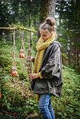 Mädchen hängt selbstgemachte Vogelfutterstation im Wald auf