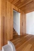 Wood-clad walls and ceilings in the hallway with stairs