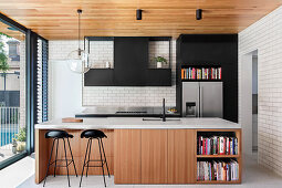Open kitchen with fronts in wood and black in front of the window front