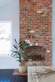 Branches in front of the rustic open brick fireplace