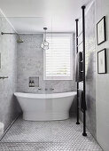 Freestanding bathtub in small, elegant gray bathroom