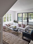 Glance into the living room with white sofa and window front to the garden