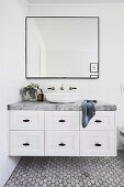 Wash basin on base cabinet with marble top and drawers
