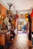 Stuffed ram and stag heads on wall above antique wooden sideboard in hallway