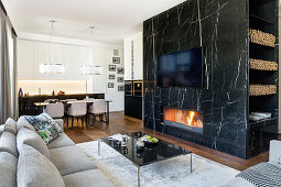 Marble wall with integrated fireplace below TV in elegant interior
