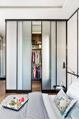 View across double bed to walk-in wardrobe with sliding doors