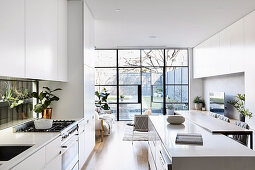 Spacious open white kitchen with island and breakfast bar