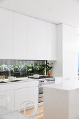 Simply modern white kitchen with plant terrarium as the back wall of the kitchen