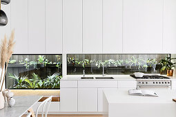 Open modern white kitchen with plant terrarium as a kitchen back wall