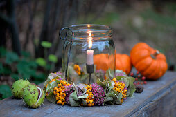 Candle lantern with wreath of sedum, hydrangeas and rowan berries next to ornamental gourds and horse chestnuts