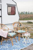 Two bamboo chairs and folding table outside renovated 80s caravan
