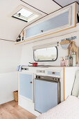 Pale blue kitchen area in lovingly renovated 80s caravan
