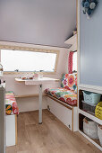 Retro-style floral couches in renovated 80s caravan