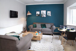 Living room with grey sofa set, dining table and chairs and petrol-blue wall