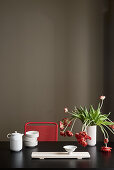 White crockery and vase of tulips on black table in front of dark wall
