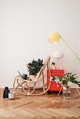 Rattan rocking chair, house plant, watering can, red cabinet and standard lamp
