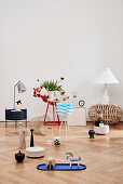 Various ornaments on side table and on pale parquet flooring