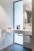 Washstand in front of floor-to-ceiling window in elegant bathroom