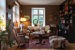 Antique sofa, elegantly patterned wallpaper and bookcase in living room