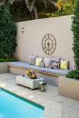 Clock on screen wall with integrated bench next to pool in garden
