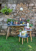 Eclectic collection of bottles, glasses and containers in front of stone wall in garden