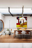 Dining area in designer apartment with dining table, round window and abstract wall painting