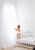 White baby room with crib and floor-to-ceiling sheer curtains