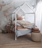 Fairytale children's room in natural tones with a cot in the shape of a house