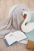 Gray pouf, cozy blanket and swan soft toy in children's room