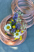 Posy of wild summer flowers in roll of copper wire