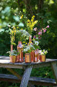 Wildflowers in copper-coloured containers on wooden table in garden