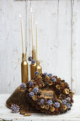 Bottles sprayed gold and used as candlesticks behind handmade wreath of pine cones