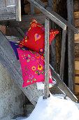 Farbenfrohe Zierkissen folkloristisch dekoriert mit Filzblüten und Filzherzen