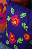 Farbenfrohe Zierkissen folkloristisch dekoriert mit Filzblüten und Filzblättern