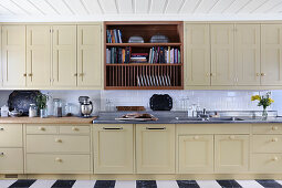 Long kitchen counter with beige panelled doors in country-house style