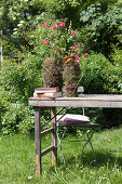 Summer flowers in decoratively wrapped vases on wooden table in garden
