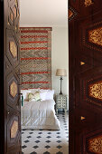 View through old wooden door into Oriental bedroom