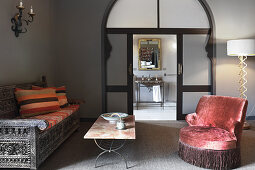 Oriental seating area in front of arched doorway leading into bathroom