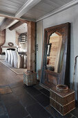 Rustic full-length mirror in hallway next to open doorway leading into dining room with fireplace