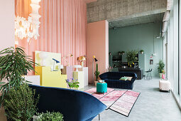 Open-plan interior with walls in pastel shades and exposed concrete ceiling